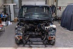 Черный автомобиль в теле фургона подготавливает для красить тело с помощью выравнивать в местах повреждения к стоковые фотографии rf