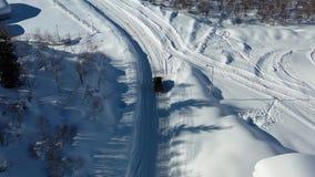 Черный автомобиль управляет вне городка на дороге покрытой снегом, во видеоматериал
