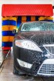 Черный автомобиль в автоматической мойке, поворачивающ голубое и желтое brushe Стоковые Фото