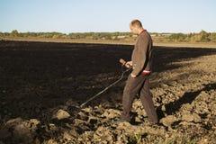 Черный археолог с металлоискателем в его руках идет через поле и поиски для драгоценностей и реликвий стоковые изображения