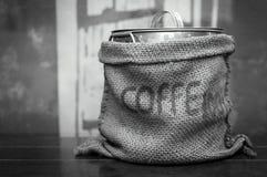 Черный & белый мешок кофе цвета тона на деревянном столе Стоковые Изображения