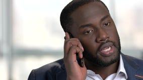Черный бизнесмен имея серьезный телефонный разговор акции видеоматериалы
