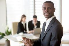 Черный бизнесмен используя цифровую таблетку на встрече Стоковая Фотография RF