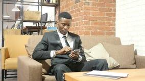 Черный бизнесмен используя Smartphone, крытый акции видеоматериалы