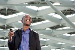 Черный бизнесмен смеясь над с мобильным телефоном стоковые фотографии rf