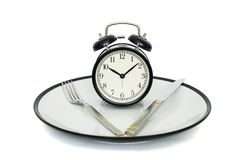 Черный будильник с вилкой и нож на плите Изолировано на белизне съешьте время к Потеря веса или концепция диеты стоковое изображение
