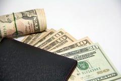 Черный бумажник с банкнотами денег и крена США использует круглую резинку на белой предпосылке Стоковые Фотографии RF