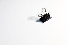 Черный бумажный зажим на белой предпосылке Стоковые Фото