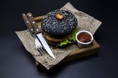 Черный бургер Бургер с кусками черными крена сочной мраморной говядины, сплавленного сыра, свежего салата и соуса барбекю Бургер Стоковое фото RF