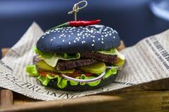 Черный бургер Бургер с кусками черными крена сочной мраморной говядины, сплавленного сыра, свежего салата и соуса барбекю Бургер Стоковые Фото