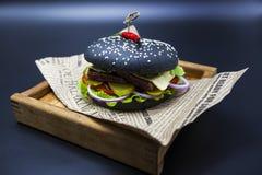 Черный бургер Бургер с кусками черными крена сочной мраморной говядины, сплавленного сыра, свежего салата и соуса барбекю Бургер Стоковые Изображения RF