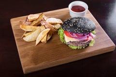 Черный бургер на доске Стоковая Фотография RF