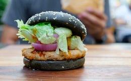 Черный бургер с свининой и пряным соусом Стоковое Фото