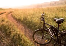 Черный велосипед страны на восходе солнца или заходе солнца Стоковые Изображения