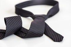 Черный галстук завязанный в форме петли на белой предпосылке Жулик стоковое фото