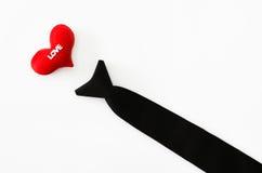 Черный галстук с красным сердцем на белом backgrond, деятельности влюбленности, влюбленности Стоковое фото RF