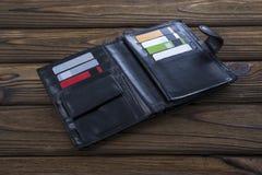 Черный естественный кожаный бумажник, на деревянной предпосылке таблицы Стоковое Изображение RF