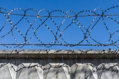 Черный затрапезный колючий провод металла на проводах на загородке против голубого неба стоковая фотография rf