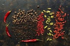 Черный и болгарский перец, перец chili, кардамон и ягоды goji на темной предпосылке spices разнообразие над взглядом стоковые изображения rf