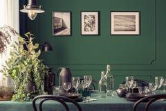 Черный и зеленый дизайн элегантного обеденного стола в модном интерьере с галереей плакатов на стене стоковое изображение rf