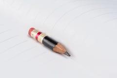 Черный карандаш с розовым ластиком на бумаге Стоковые Изображения RF