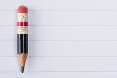 Черный карандаш с розовым ластиком на бумаге Стоковые Фото
