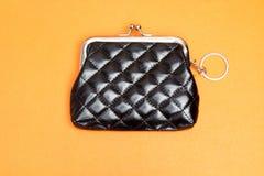 E Черный кожаный бумажник на оранжевой предпосылке стоковое фото rf