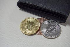 Черный кожаный бумажник на таблице с монетками bitcoins падая из их карманов Концепция секретных валют стоковое фото rf