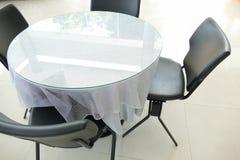 Черный кожаный стул и круглый стол с серой скатертью Стоковая Фотография RF