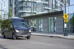 Черный компактный коммерчески мини фургон управляя на городской улице города стоковое изображение rf