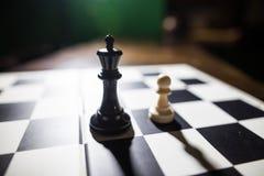 Черный король и белая пешка на шахматной доске Стоковые Изображения RF