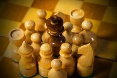 Черный король шахмат окруженный белыми частями Стоковые Фото
