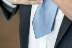 Черный костюм, белая рубашка и голубая концепция дела связи, финансовых или политичных вручают связывать вверх Стоковая Фотография