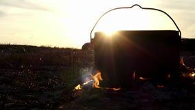 Черный котел стоит в лагерном костере Оно кипит горячую воду на заходе солнца в замедленном движении акции видеоматериалы