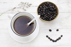 Черный кофе в белых чашке и кофейных зернах с белой ложкой и стоковое изображение