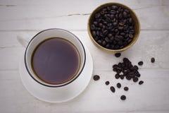 Черный кофе в белых чашке и кофейных зернах стоковое фото rf
