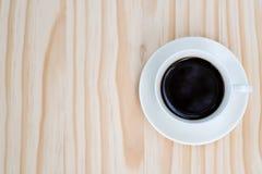 Черный кофе в белой чашке на деревянной предпосылке Стоковое Изображение
