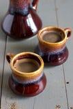 Черный кофе в коричневых и серых керамических чашках Стоковое фото RF