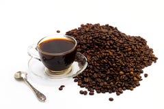 Черный кофе в стеклянной чашке и зернах кофе на белой предпосылке Стоковая Фотография