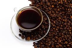 Черный кофе в стеклянной чашке и зернах кофе на белой предпосылке Стоковая Фотография RF