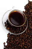Черный кофе в стеклянной чашке и зернах кофе на белой предпосылке Стоковые Изображения