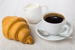Черный кофе в чашке, ложке на поддоннике, круассане, молоке Стоковая Фотография RF