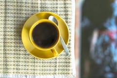 Черный кофе на циновке и расплывчатом бассейне имея карпов Стоковое фото RF