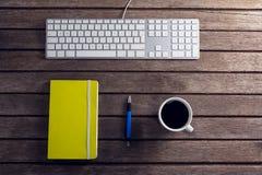 Черный кофе, ручка, организатор и клавиатура на деревянном столе Стоковые Фотографии RF