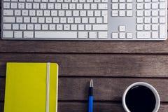 Черный кофе, ручка, организатор и клавиатура на деревянном столе Стоковые Изображения