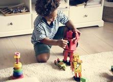 Черный мальчик играя роботы дома стоковое изображение