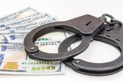 Черный металл надевает наручники лежать на 100 долларах банкнот на белой предпосылке Стоковое Изображение RF