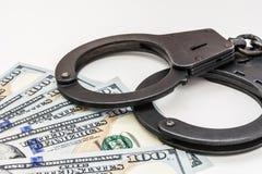 Черный металл надевает наручники лежать на 100 долларах банкнот на белой предпосылке Стоковое фото RF