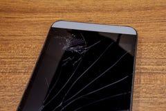 Черный мобильный телефон на деревянном столе с, который разбили дисплеем lcd Передвижная концепция технологии Разрушенный smartph Стоковые Изображения RF