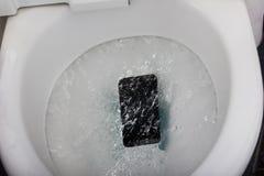 Черный мобильный телефон падая в топить туалета стоковая фотография rf